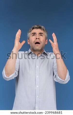 Studio shot of desperate businessman with hands up. Adult man lifted hands isolated over blue background - stock photo