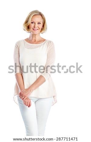 Studio shot of elegant mature woman standing on white background - stock photo