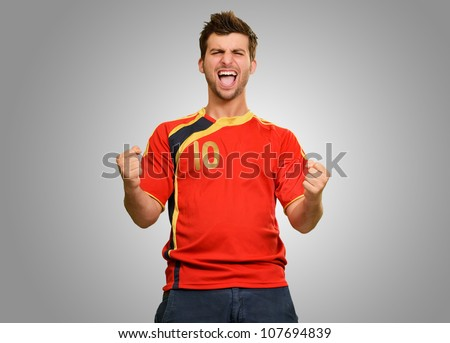 Studio Shot Of Excited Young Player Isolated On Grey Background - stock photo