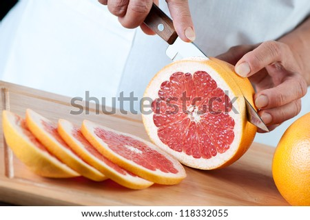 Studio shot of female hands slicing a ripe grapefruit - stock photo