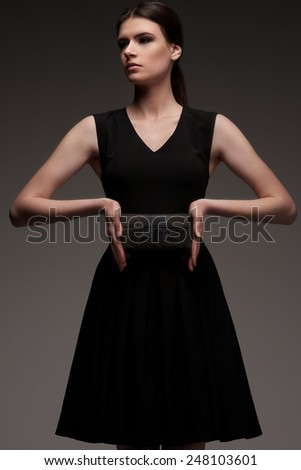 Studio shot of Female model in black designer fashion dress with clutch stay on gray background