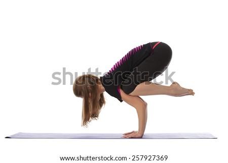 Studio shot of flexible woman doing yoga handstand - stock photo