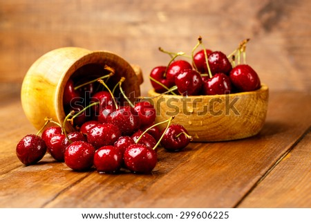 Studio shot of fresh natural cherries on wooden background