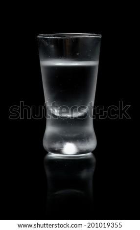 Studio shot of glass of vodka isolated on black background - stock photo