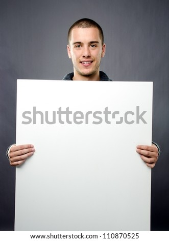 Studio shot of handsome young man with blank white board - stock photo