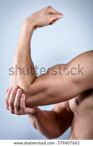 Studio shot of handsome young man with naked torso. Man suffering from arm ache