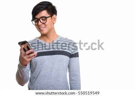 Studio shot of happy Asian man smiling while using mobile phone isolated against white background