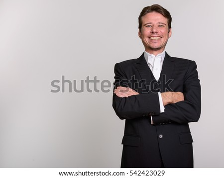 Studio shot of happy Caucasian businessman smiling with arms crossed against gray background