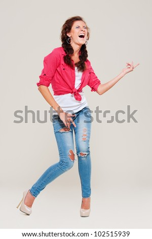 studio shot of happy woman playing air guitar over grey background - stock photo
