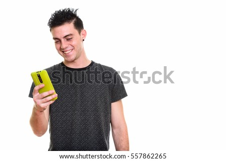 Studio shot of happy young man smiling while using mobile phone isolated against white background