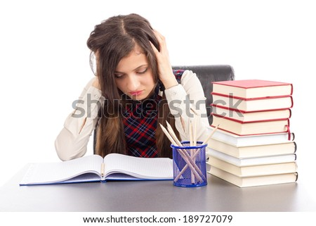 Studio shot of hopeless student with hands on head sitting at his desk  isolated over white background - stock photo