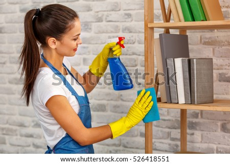 Studio shot of housekeeper. Beautiful woman cleaning shelf at office and smiling