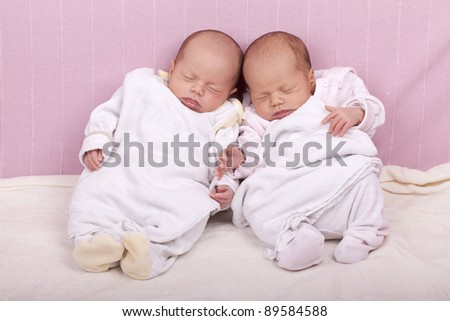studio-shot of identical ( similar ) newborn twin girls sleeping on a sofa. - stock photo