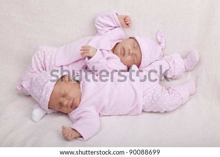 studio-shot of identical twin girls sleeping on a sofa. - stock photo