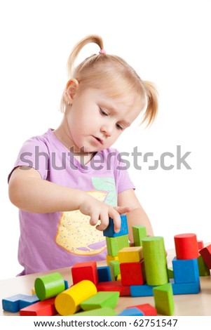 studio shot of little girl playing with toy blocks - stock photo