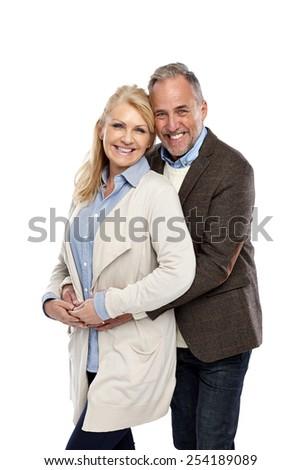 Studio shot of loving mature couple embracing on white background - stock photo