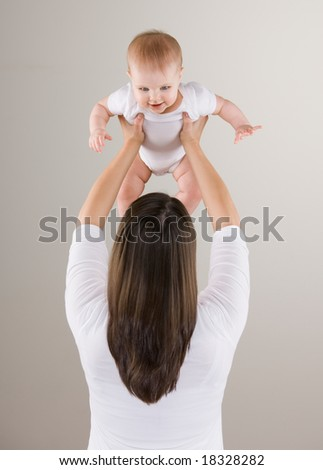 Studio shot of loving mother lifting smiling baby above head - stock photo