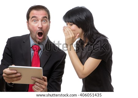 Studio shot of male and female co-workers using a tablet computer.  Female model is whispering into her male colleagues ear, leaving him with a startled expression.     - stock photo