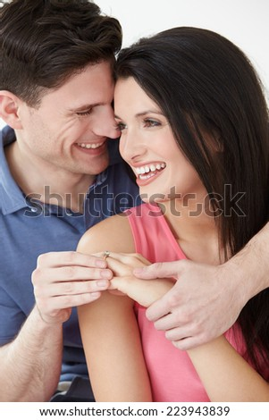 Studio Shot Of Man Putting Ring On Woman's Finger - stock photo