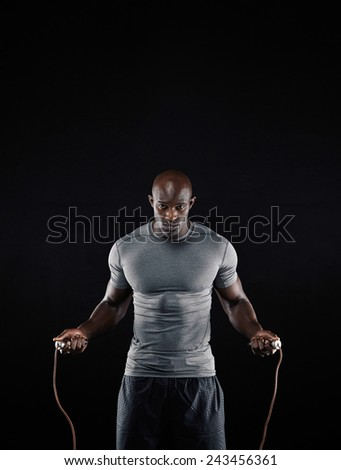 Studio shot of masculine african man skipping rope with copyspace. Portrait of muscular young man exercising with jumping rope on black background - stock photo