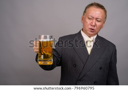 Studio shot of mature Asian businessman holding glass of beer against gray background