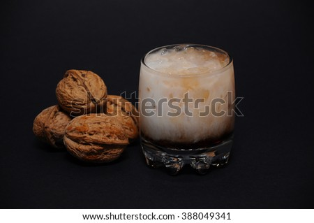Studio shot of Milky Volcano cocktail in small tumbler glass next to four walnuts on a pile, on black background. - stock photo