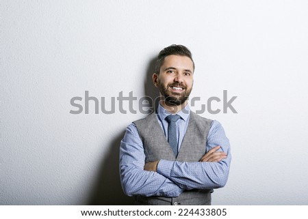 Studio shot of modern hipster businessman leaning against wall - stock photo