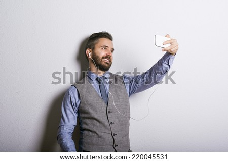 Studio shot of modern hipster businessman taking selfie with mobile phone - stock photo