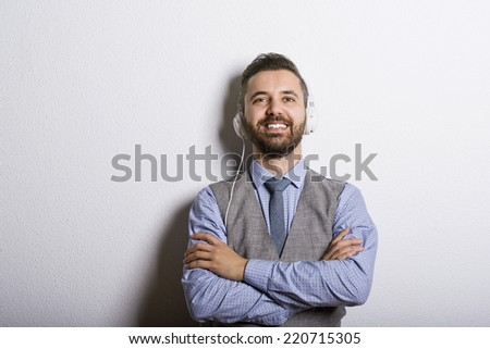 Studio shot of modern hipster businessman with headphones, listening to music - stock photo
