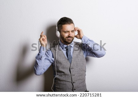 Studio shot of modern hipster businessman with headphones, listening to music and dancing - stock photo