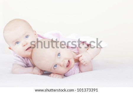 studio-shot of 6 month old identical baby twin sisters lying on bed and learning how to crawl.