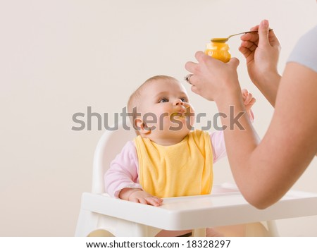 Studio shot of mother feeding hungry baby in highchair - stock photo