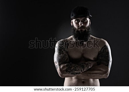 Studio shot of Muscular Man with tattoo  and  baseball cap on dark background - stock photo