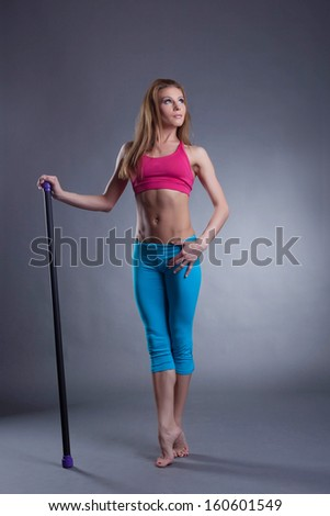 Studio shot of muscular strong woman with fitbar - stock photo