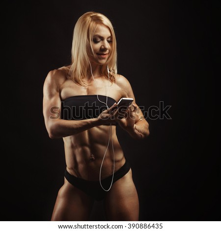 Studio shot of muscular young woman listening music on mobile phone against black background. Attractive blond bodybuilder with a mobile phone. Space for text