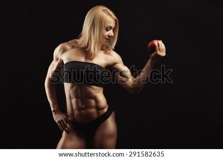 Studio shot of muscular young woman with blond hair in her right hand holding a red apple. Space for text on the right side - stock photo