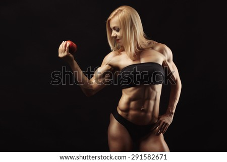 Studio shot of muscular young woman with blond hair in her right hand holding a red apple. Space for text on the left side - stock photo