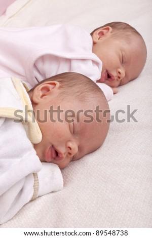 studio-shot of newborn identical ( similar) twin girls. - stock photo