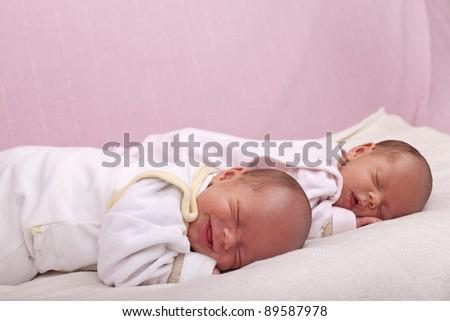 studio-shot of newborn identical ( similar) twin girls sleeping on a sofa.
