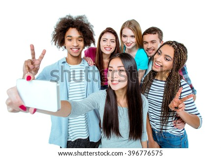 Studio shot of nice young multicultural friends. Beautiful people cheerfully smiling and having fun while making selfie photo on mobile phone. Isolated background - stock photo