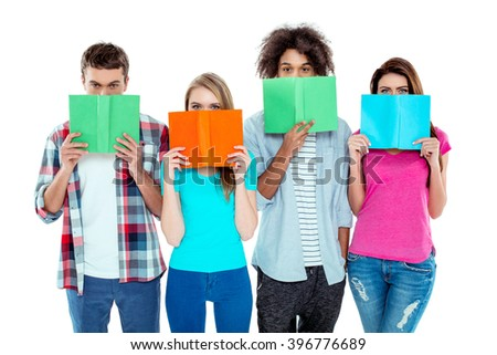 Studio shot of nice young multicultural friends. Beautiful people hiding behind books and looking at camera. Isolated background - stock photo