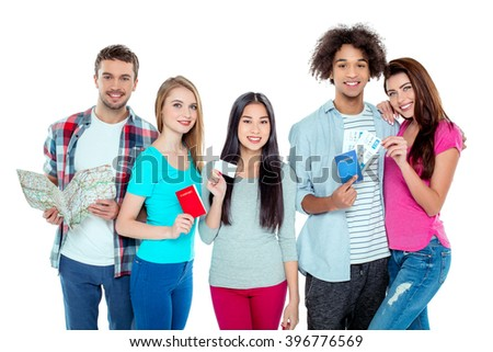 Studio shot of nice young multicultural friends. Beautiful people looking at camera, holding tickets, passports, map, visit card and smiling. Isolated background - stock photo