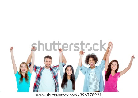Studio shot of nice young multicultural friends. Beautiful people looking at camera, holding hands up and cheerfully smiling. Isolated background. Free space for your logo - stock photo