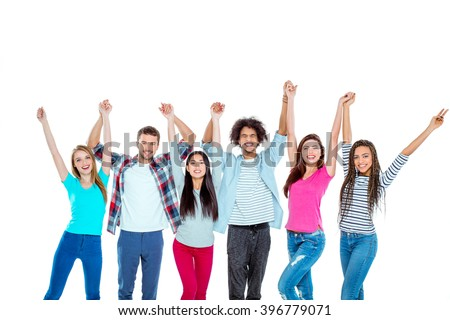 Studio shot of nice young multicultural friends. Beautiful people looking at camera, holding hands up and cheerfully smiling. Isolated background - stock photo