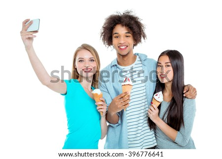 Studio shot of nice young multicultural friends. Beautiful people looking at camera, smiling, making selfie photo on mobile phone and holding ice-creams. Isolated background - stock photo