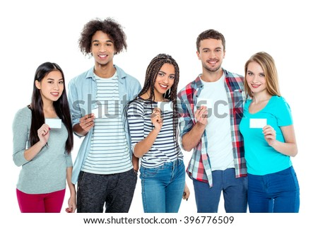 Studio shot of nice young multicultural friends. Beautiful people looking at camera, smiling and holding empty visit cards. Isolated background - stock photo