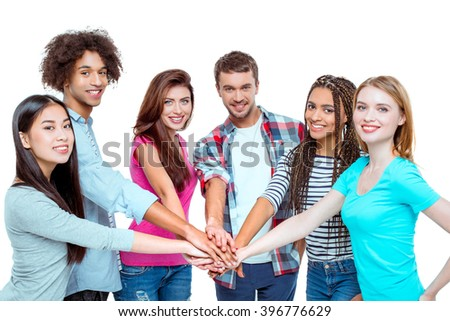 Studio shot of nice young multicultural friends. Beautiful people putting hand on hand, looking at camera and cheerfully smiling. Isolated background