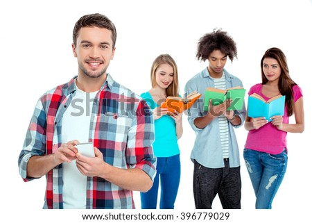 Studio shot of nice young multicultural friends. Beautiful people reading books. One boy using mobile phone, looking at camera and smiling. Isolated background - stock photo