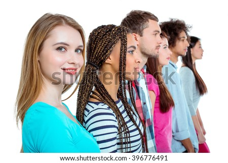 Studio shot of nice young multicultural friends. Beautiful people standing in a row. Focus on blonde woman. Girl looking at camera and smiling. Isolated background - stock photo