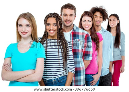 Studio shot of nice young multicultural friends. Beautiful people standing in a row, looking at camera and smiling. Isolated background - stock photo